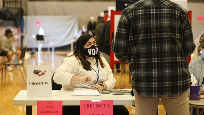 Election official Amanda Colligan checks voters in at Precinct 4 in the gymnasium of East Bridgewater Jr/Sr High School on Election Day, Tuesday, Nov. 3, 2020.