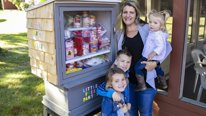 Holly Richard of Raynham and her children Ella Jope, 4, William Jope, 6, and Sophie Jope, 19 months, keeps the Little Free Pantry her father Jim built at 75 Mill St. stocked for residents of the Raynham Housing Authority apartments on Wednesday, Oct. 21, 2020. Community members are also collecting donations to stock the pantry.