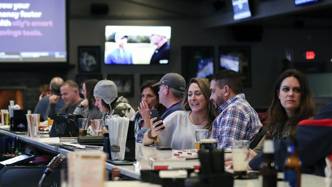 FILE - Patrons enjoy a drink at Barrett's Alehouse in West Bridgewater on Monday night, March 16, 2020, the last day for on-premises consumption due to the coronavirus.