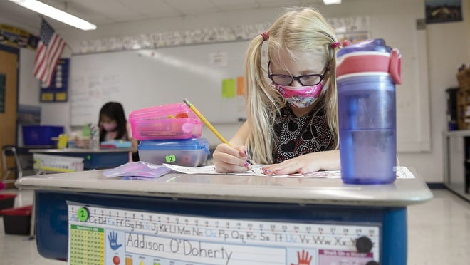 FILE - Addison O'Doherty draws while wearing her face mask in class at the Louise A. Conley Elementary School in Whitman on the first day of school, Tuesday, Sept. 15, 2020.