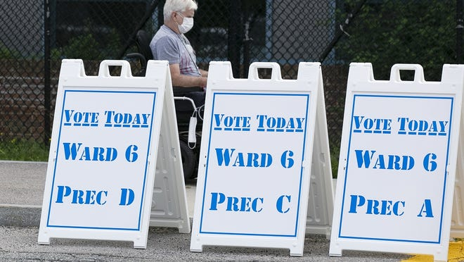In this Tuesday, Sept. 1, 2020, file photo, a voter is seen wearing a mask outside the Brookfield Elementary School during the primary election.