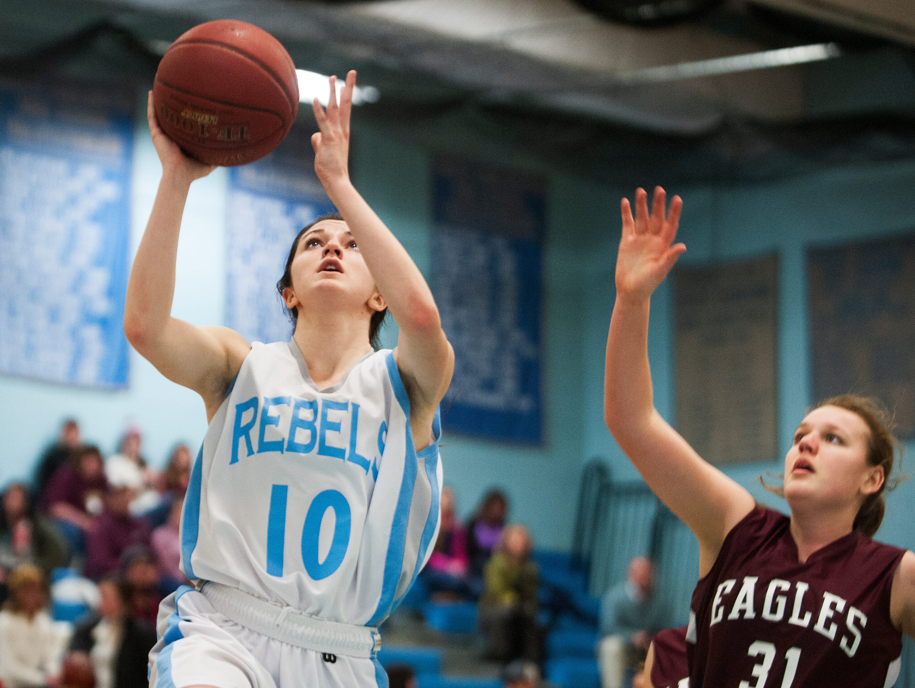 South Burlington's Kayla Gilding, left, leaps past Mt. Abraham's Isabel Brennan (31) for a lay up during the girls basketball game.