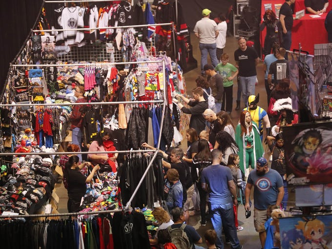 People look at exhibit booths at Ace Comic Con at Gila