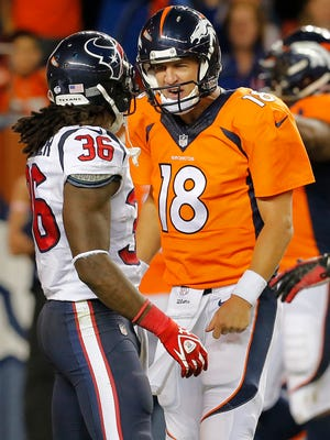 Denver Broncos quarterback Peyton Manning (18) talks to Houston Texans strong safety D.J. Swearinger (36) after a Broncos touchdown during the first half of an NFL preseason football game, Saturday, Aug. 23, 2014, in Denver. Manning was whistled and fined for taunting.