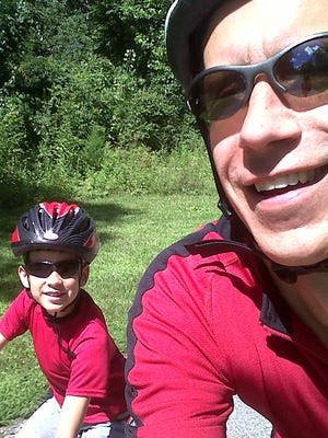 Ron Plush, right, with his son, Kyle, riding bicycles on the Little Miami Trail.
