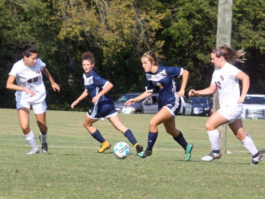 Seymour's Linnea Egner dribbles upfield with teammate Abbie Biddle to her right.