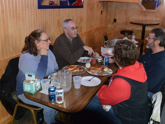 A group of friends gather for pizza and drinks at Bell Mell's in Port Clinton.