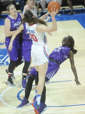 ACU's Suzzy Dimba (23) falls to the court as SMUs Alicia  Froling (10) shoots in the second half. SMU beat the Wildcats 59-52 in the second round of the WNIT on Monday, March 20, 2017 at Moody Coliseum in Dallas.