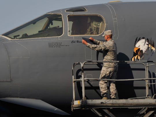 Senior Airman Jesse Barnhill removes the name of Colonel