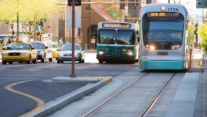 Michael Schennum A city bus and light rail train travel on Central Avenue in downtown Phoenix.