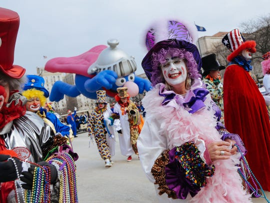 Members of the Distinguished Clown Corps walk along Woodward ave. while passing out beads during the 2014 America's Thanksgiving Parade on Thursday November 27, 2014.