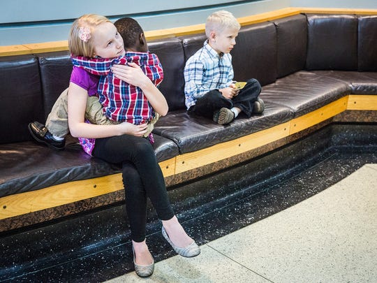 Isaiah (middle) with his siblings at the Delaware County Justice Center waiting to be officially adopted on Adoption Day Thursday, Nov. 19, 2015.