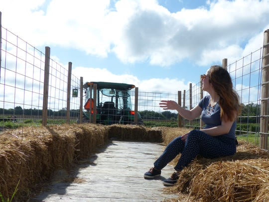 Reporter Ashley Collins rides a hay trailer to Farmer