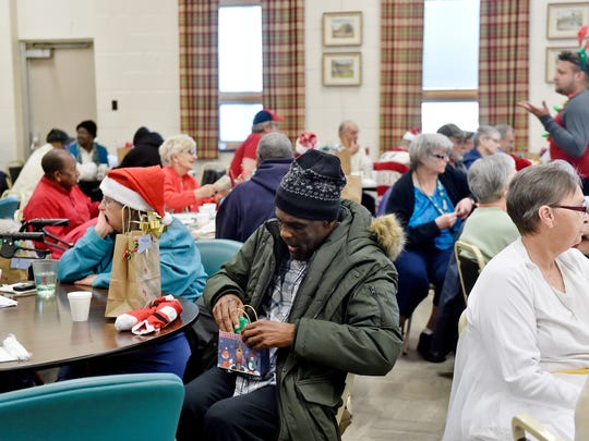 Alvin Johnson, 54, of York, opens his gift bag at the White Rose Senior Center in York. The gifts came from three sisters who collected donations and spent their own money.