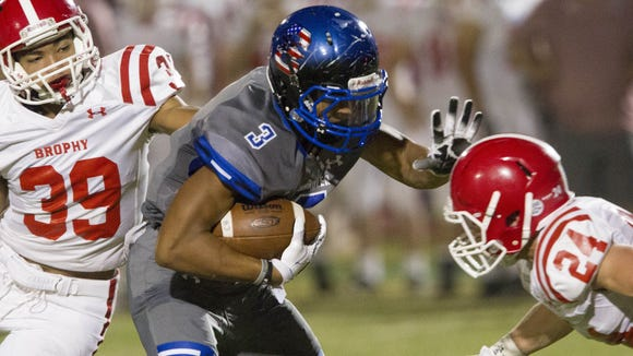 Chandler High senior ATH Johnny Johnson III (3) makes a first down in the first half as Brophy College Prep sophomore SS Marques White (39) and senior FS Hunter Trueman (24) close in at Chandler High School in Chandler on Friday, Oct. 21, 2016.