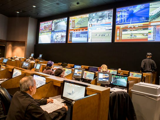 Gamblers watch races on a wall of televisions in the