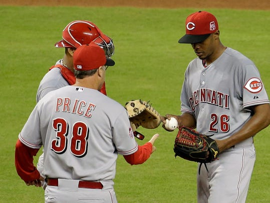 Cincinnati Reds starting pitcher Raisel Iglesias (26) hands the ball to manager Bryan Price (38) in the fifth inning of a baseball game against the Miami Marlins, Saturday, July 11, 2015, in Miami. The Marlins defeated the Reds 14-3. (AP Photo/Lynne Sladky)