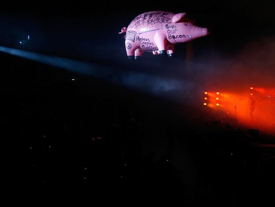 A giant pig-shaped balloon floats as Roger Waters,