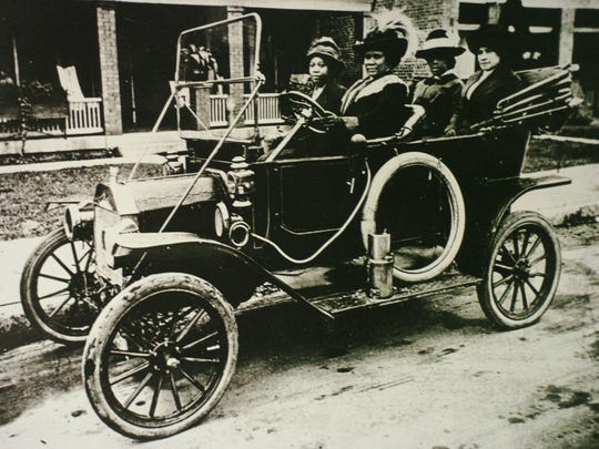Copy of a photograph of Madam CJ Walker driving an automobile displayed in the Heritage center in the Walker Theatre.