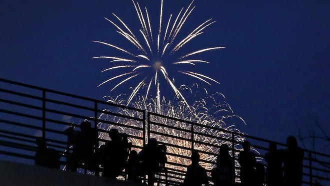 People watch the CarmelFest fireworks show from the elevated Monon Greenway over East 126th Street as the Carmel Symphony provides the music. It was a perfect ending to Carmel's two-day Fourth of July celebration on Saturday night, July 4, 2015.