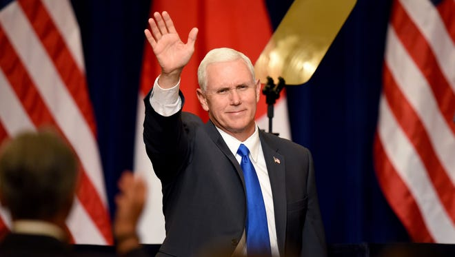 Vice President Mike Pence waves his hand before delivering a speech during a meeting with Japanese and U.S. business leaders in Tokyo on April 19, 2017.