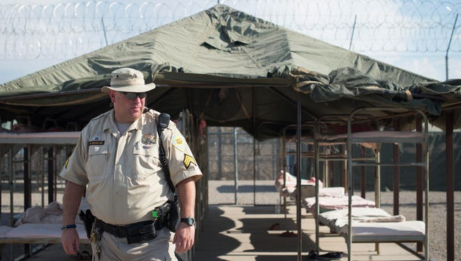 A guard stands in front of rows of empty bunks at Tent City Jail during an event celebrating the jail's 20th year in operation on Aug. 3, 2013, in Phoenix.
