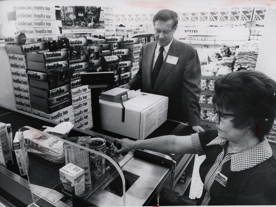 Robert Wegman watches Margo Capriotti operate new checkout scanner capable of reading Universal Product Codes at the East Rochester Wegmans in 1974.