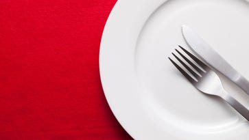 A stock image of a plate, knife and fork against a red background.