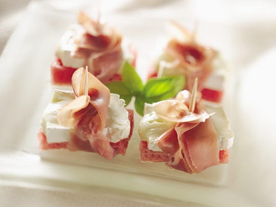 Easy appetizers: watermelon fingers topped with brie and wrapped in prosciutto.