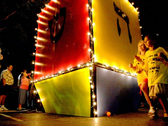 Eight-year-old Hailey Morstein, right, and Michelle Indianer, 7, far right, walk past an 18-foot dreidel during the Chabad Jewish Center of Naples' Hanukkah celebration at The Village on Venetian Bay in 2007.