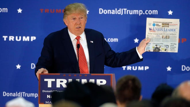 Republican presidential candidate Donald Trump displays a copy of the Union Leader newspaper while addressing an audience during a campaign event Monday, Dec. 28, 2015, in Nashua, N.H. New Hampshire's largest newspaper, the Union Leader, is the latest target of Trump's attacks against the news media. (AP Photo/Steven Senne)