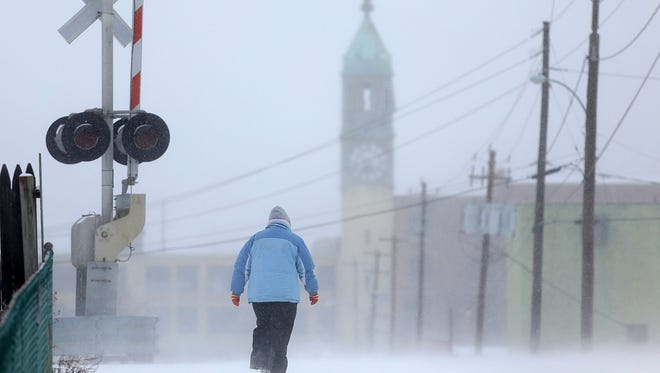 Wind and snow whip by Virginia Nolan of Scranton as makes her way to work through a snow squall near the former Scranton Lace Company building in Scranton, Pa.,