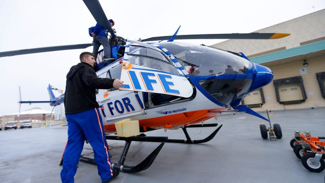 Flight For Life pilot Anders Vetch steps out of a Flight For Life helicopter as mechanic JJ Hoffmann prepares to fold in the blades after the helicopter landed on the roof of the Wisconsin Center.