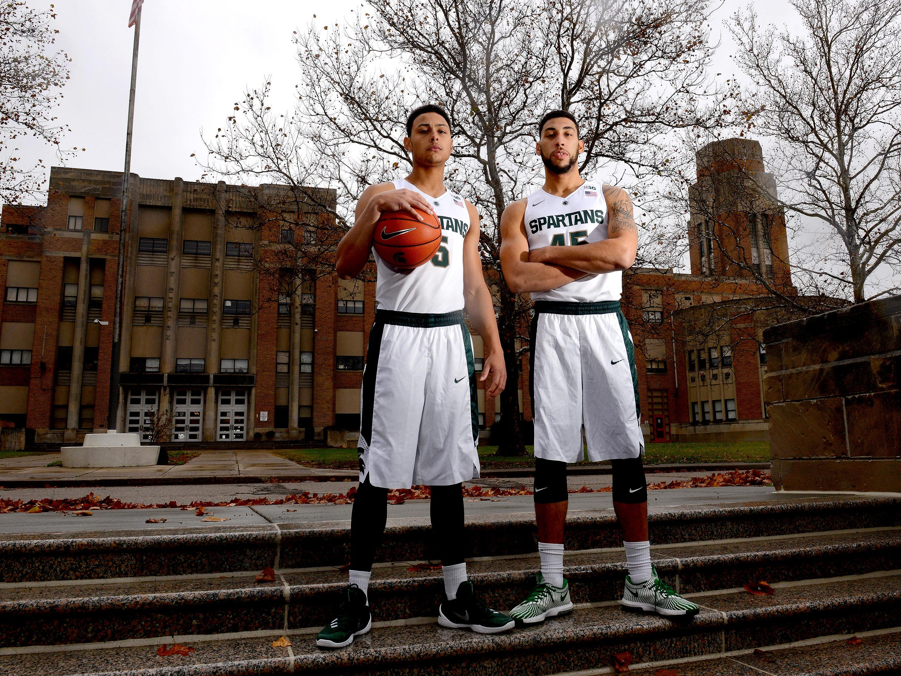 Michigan State basketball players Bryn Forbes, left, and Denzel Valentine, right, stand outside their alma mater, Lansing Sexton High School. The pair one two state titles there.