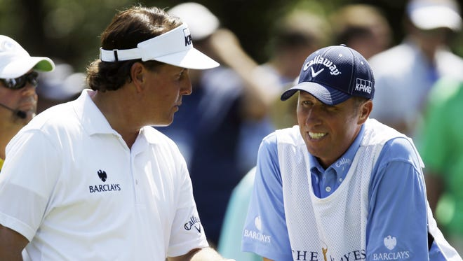 Phil Mickelson, left, talks to his caddie Jim Mackay while waiting to hit from the eighth tee during the first round of The Players Championship last year.