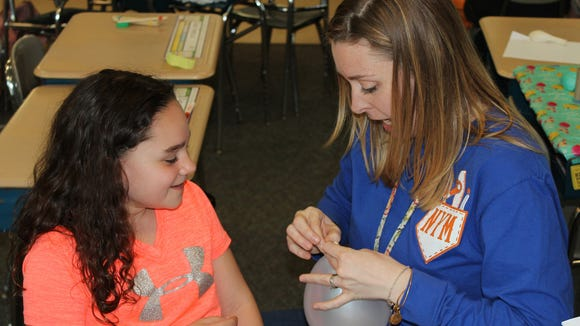 Mrs. Gibbs helps Makenna tie off a balloon to measure lung capacity (J. Baier)
