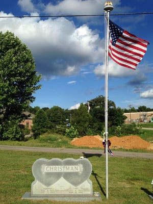 An American flag flies to honor Carl Christman for his military service at Camden City Cemetery on Monday.