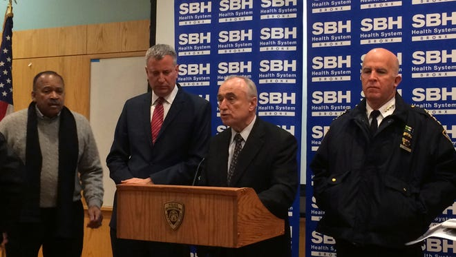 New York City Mayor Bill de Blasio, second left, stands by as Police Commissioner William Bratton, second right, speaks at a news conference at St. Barnabas Hospital in the Bronx section of New York City after two New York City police officers were shot. The two officers responding to a robbery in the Bronx were shot and wounded Monday night, and a manhunt was underway for at least two suspects, authorities said. The officers were taken to the hospital with non-life threatening injuries.