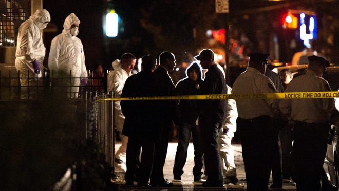 New York City police officers investigate the scene where four children and their mother were stabbed to death in Brooklyn.