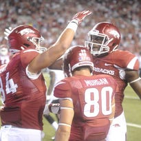 Arkansas tight ends Hunter Henry, left, and Jeremy Sprinkle, right, and receiver Drew Morgan (80) celebrate after a touchdown against Texas Tech.