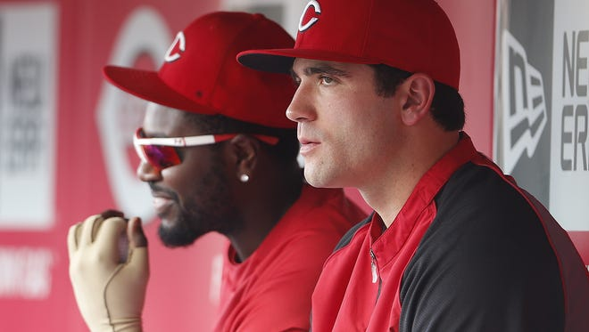 Cincinnati Reds first baseman Joey Votto (19), left, and second baseman Brandon Phillips (4), chat with one another in the dugout.