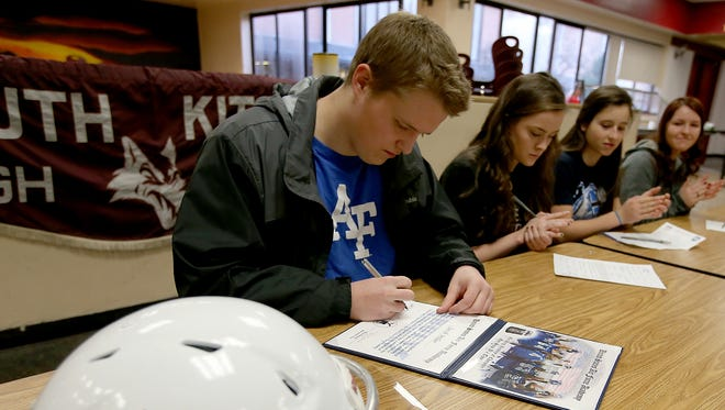 South Kitsap football player Jacob Miller signs his certificate of intent to play football for Air Force on Wednesday. Also signing their letters were Mikaela Morey, Mylie LaFountaine and Emily Miller.