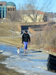 Mary Nezt walks along the River's Edge Trail with her