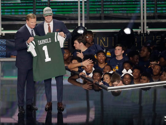 Commissioner Roger Goodell, left, presents Southern California's Sam Darnold with his New York Jets jersey during the first round of the NFL football draft, Thursday, April 26, 2018, in Arlington, Texas.