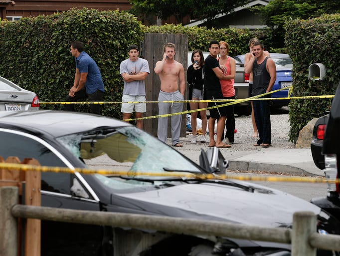 People look at a black BMW sedan driven by a drive-by shooter in Isla Vista, Calif.