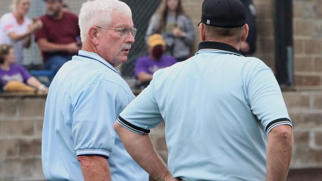 MSHSAA home plate umpire Kelly Odneal turns his head to visit with field official Bob Roberts during a Moberly home softball game played earlier this 2020 fall season. Each official is a prominent retired coaches and members of the Missouri Sports Hall of Fame as well as respective high school coaches hall of fame inductees for softball and basketball. Odneal coached softball at Westran in Huntsville and Roberts coached basketball at Northeast R-IV School at Cairo.