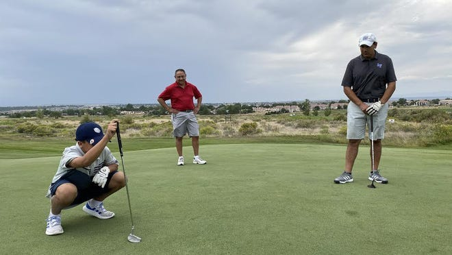 Xan Garcia lines up a putt as Vince Guerrero (middle) and Xan's father, Senate President Leroy Garcia (right), watch on during a golf tournament held Friday at Walking Stick Golf Course to benefit 4-H and FFA.
