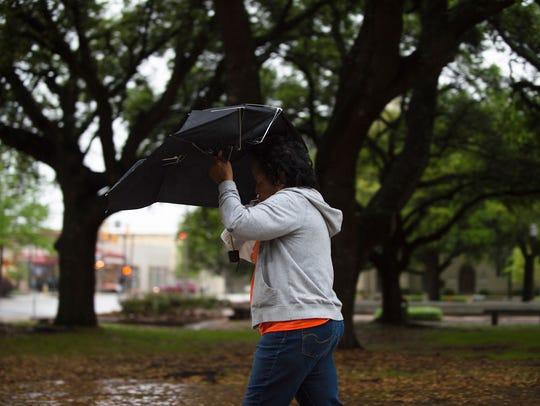 A pedestrian walks through the rain on Monday, April