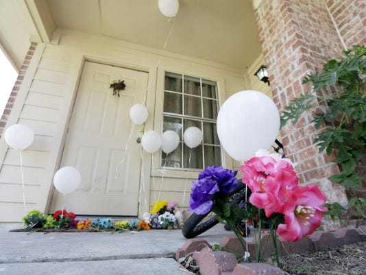 Flowers and eight balloons are seen at a house, Sunday, Aug. 9, 2015, where eight people were killed on Saturday in Houston. A family of six children and two parents were handcuffed and fatally shot in the head at a Houston home by a man with a violent criminal history who had previously been in a relationship with the mother and had a dispute with her, authorities said Sunday. David Conley, 48, was charged with capital murder in the deaths.