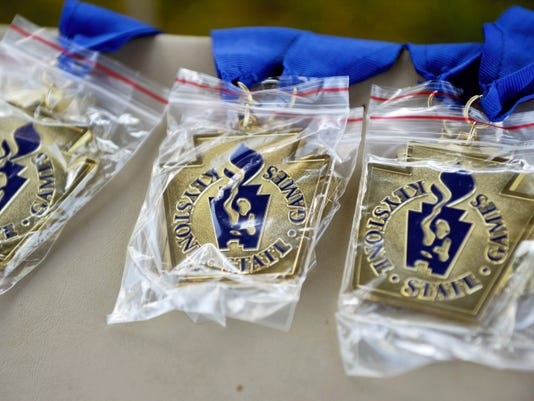 Gold medals for the football/softball toss event are prepared on the second day of the 2015 Keystone State Games. The multi-day event bills itself as the state's largest amateur sports festival, with about 30 different sports being played in York County.